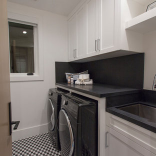 This is an example of a medium sized beach style galley separated utility room in Orange County with a submerged sink, shaker cabinets, white cabinets, composite countertops, white walls, vinyl flooring, a side by side washer and dryer, multi-coloured floors and black worktops.