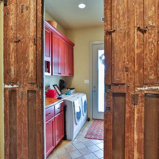 Idéer för mellanstora lantliga tvättstugor, med röda skåp, träbänkskiva, klinkergolv i keramik, en tvättmaskin och torktumlare bredvid varandra, luckor med infälld panel och beige väggar