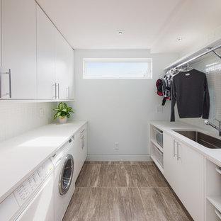 Immagine di una sala lavanderia minimal di medie dimensioni con ante bianche, lavello sottopiano, ante lisce, top in quarzite, pareti bianche, pavimento in vinile, lavatrice e asciugatrice affiancate, pavimento marrone e top bianco
