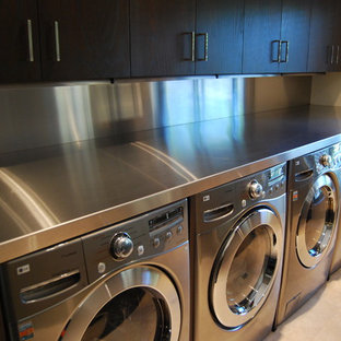 Example of a mid-sized classic single-wall travertine floor and beige floor dedicated laundry room design in Chicago with flat-panel cabinets, dark wood cabinets, stainless steel countertops, a side-by-side washer/dryer and white walls