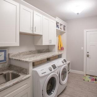 Idéer för stora amerikanska linjära grått grovkök, med en undermonterad diskho, skåp i shakerstil, vita skåp, marmorbänkskiva, grå väggar, klinkergolv i keramik, en tvättmaskin och torktumlare bredvid varandra och beiget golv