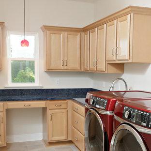 Foto på ett stort blå l-format grovkök, med en undermonterad diskho, luckor med upphöjd panel, skåp i ljust trä, beige väggar, en tvättmaskin och torktumlare bredvid varandra och beiget golv