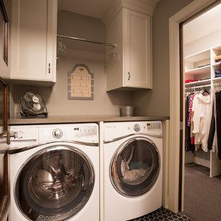 Foto på en vintage tvättstuga enbart för tvätt, med luckor med infälld panel, vita skåp, grå väggar och en tvättmaskin och torktumlare bredvid varandra