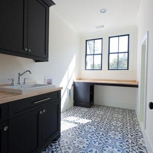 Klassisk inredning av en mellanstor l-formad tvättstuga enbart för tvätt, med en nedsänkt diskho, skåp i shakerstil, svarta skåp, träbänkskiva, vita väggar, klinkergolv i keramik, en tvättmaskin och torktumlare bredvid varandra och flerfärgat golv