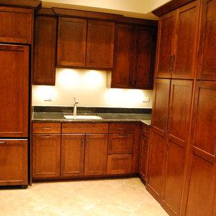 Esempio di un'ampia lavanderia multiuso chic con lavello sottopiano, ante in stile shaker, top in granito, pavimento con piastrelle in ceramica, lavatrice e asciugatrice nascoste, pareti beige e ante in legno bruno