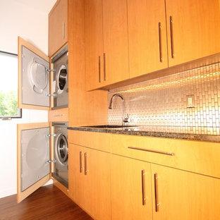 Пример оригинального дизайна: параллельная прачечная в стиле модернизм с врезной раковиной, плоскими фасадами, гранитной столешницей, белыми стенами, полом из бамбука и с сушильной машиной на стиральной машине