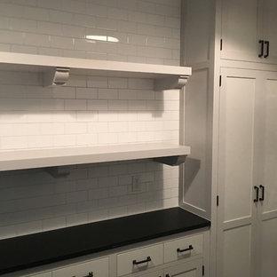 Idee per una sala lavanderia classica di medie dimensioni con ante con riquadro incassato, ante bianche, top in superficie solida, pareti bianche, lavatrice e asciugatrice a colonna e pavimento in ardesia