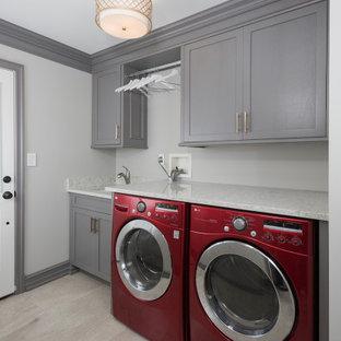 Foto på en mellanstor funkis vita linjär liten tvättstuga, med luckor med infälld panel, vita skåp, granitbänkskiva, beige väggar, laminatgolv, en tvättmaskin och torktumlare bredvid varandra, grått golv och en dubbel diskho