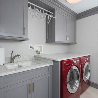 Exempel på en mellanstor modern vita linjär vitt liten tvättstuga, med en dubbel diskho, luckor med infälld panel, vita skåp, granitbänkskiva, beige väggar, laminatgolv, en tvättmaskin och torktumlare bredvid varandra och grått golv