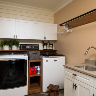Dedicated laundry room - rustic l-shaped shiplap wall dedicated laundry room idea in Other with a single-bowl sink, white cabinets, beige walls, a side-by-side washer/dryer and gray countertops