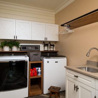Idee per una sala lavanderia rustica con lavello a vasca singola, ante bianche, pareti beige, lavatrice e asciugatrice affiancate, top grigio e pareti in perlinato