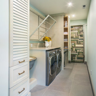 Example of a mid-sized transitional single-wall dedicated laundry room design in Seattle with an utility sink, louvered cabinets, quartz countertops, green walls and a side-by-side washer/dryer