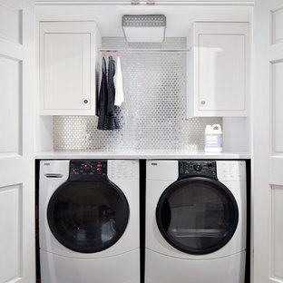 This is an example of a classic utility room in New York with white cabinets, a side by side washer and dryer and white worktops.