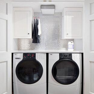 Foto di una lavanderia tradizionale con ante bianche, lavatrice e asciugatrice affiancate e top bianco