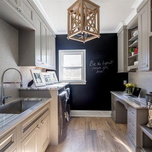 Idee per una lavanderia multiuso classica di medie dimensioni con lavello sottopiano, ante con riquadro incassato, ante grigie, top in marmo, parquet scuro, lavatrice e asciugatrice affiancate e pareti nere