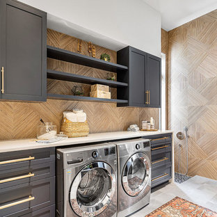 Foto på ett maritimt vit linjärt grovkök, med skåp i shakerstil, grå skåp, beige väggar, en tvättmaskin och torktumlare bredvid varandra och grått golv