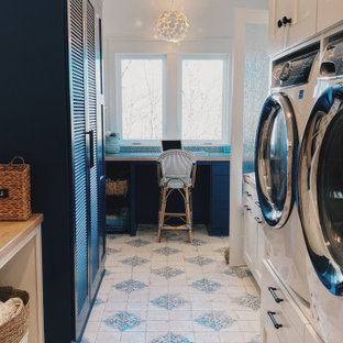 This is an example of an utility room with blue cabinets, marble benchtops, blue splashback, glass tile splashback, white walls, ceramic floors, a stacked washer and dryer, blue floor and multi-coloured benchtop.