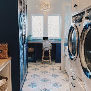 Exemple d'une buanderie multi-usage avec des portes de placard bleues, un plan de travail en marbre, une crédence bleue, une crédence en carreau de verre, un mur blanc, un sol en carrelage de céramique, des machines superposées, un sol bleu et un plan de travail multicolore.