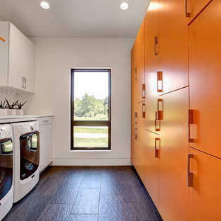 This is an example of a medium sized contemporary galley separated utility room in Grand Rapids with flat-panel cabinets, engineered stone countertops, slate flooring, a side by side washer and dryer, orange cabinets and white walls.