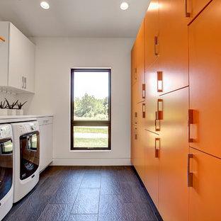Exemple d'une buanderie parallèle tendance dédiée et de taille moyenne avec un placard à porte plane, un plan de travail en quartz modifié, un sol en ardoise, des machines côte à côte, des portes de placard oranges et un mur blanc.