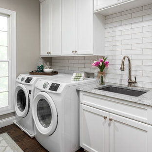 Mid-sized traditional galley utility room in St Louis with an undermount sink, flat-panel cabinets, white cabinets, quartzite benchtops, grey walls, medium hardwood floors, a side-by-side washer and dryer, brown floor and grey benchtop.