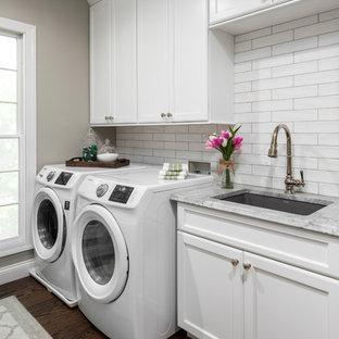 Exempel på ett mellanstort klassiskt grå parallellt grått grovkök, med en undermonterad diskho, släta luckor, vita skåp, bänkskiva i kvartsit, grå väggar, mellanmörkt trägolv, en tvättmaskin och torktumlare bredvid varandra och brunt golv