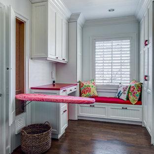 Cette photo montre une buanderie nature en U avec un placard avec porte à panneau encastré, des portes de placard blanches, un sol en bois brun et un plan de travail rouge.