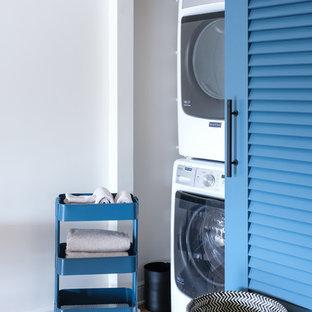 Ispirazione per un ripostiglio-lavanderia tradizionale con pavimento in legno massello medio, lavatrice e asciugatrice a colonna, pareti bianche e pavimento marrone