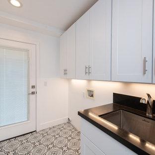 Idéer för att renovera ett mellanstort funkis svart svart grovkök, med en undermonterad diskho, luckor med upphöjd panel, vita skåp, granitbänkskiva, svart stänkskydd, vita väggar, klinkergolv i keramik och flerfärgat golv