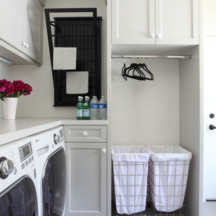 Пример оригинального дизайна: угловая прачечная в классическом стиле с серыми фасадами, фасадами с утопленной филенкой, со стиральной и сушильной машиной рядом и белой столешницей