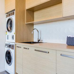 Idee per una sala lavanderia minimalista di medie dimensioni con ante lisce, top in quarzo composito, pavimento in cemento, lavello a vasca singola, ante in legno chiaro, pareti bianche, lavatrice e asciugatrice a colonna, pavimento grigio e top marrone