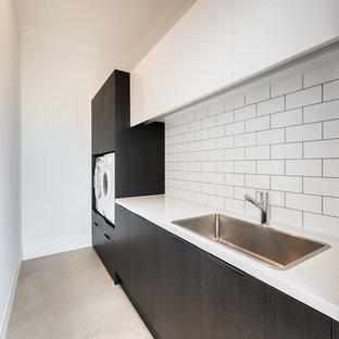 Design ideas for a large contemporary galley laundry room in Adelaide with an undermount sink, flat-panel cabinets, black cabinets, marble benchtops, white splashback, marble splashback, concrete floors and brown floor.