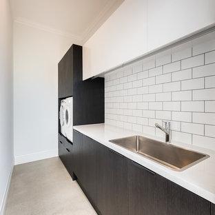 Inredning av en modern stor parallell tvättstuga, med en undermonterad diskho, släta luckor, svarta skåp, marmorbänkskiva, vitt stänkskydd, stänkskydd i marmor, betonggolv och brunt golv