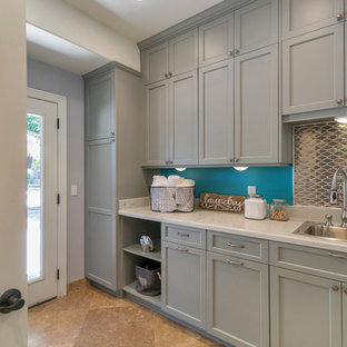Design ideas for a large contemporary dedicated laundry room in Phoenix with an undermount sink, flat-panel cabinets, grey cabinets, quartzite benchtops, grey splashback, porcelain splashback, travertine floors, grey walls and a side-by-side washer and dryer.
