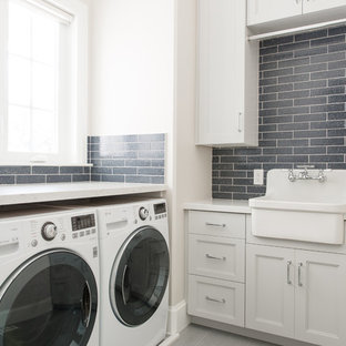 Transitional l-shaped gray floor dedicated laundry room photo in Salt Lake City with a farmhouse sink, recessed-panel cabinets, white cabinets, beige walls and white countertops
