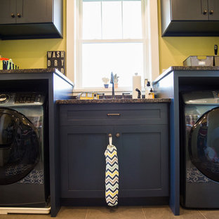 Design ideas for a medium sized traditional single-wall utility room in Other with a double-bowl sink, recessed-panel cabinets, blue cabinets, granite worktops, yellow walls, ceramic flooring, a side by side washer and dryer, beige floors and black worktops.