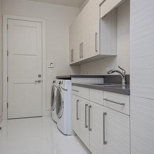 Cette image montre une buanderie linéaire minimaliste multi-usage et de taille moyenne avec un évier encastré, un placard à porte plane, un mur blanc, des machines côte à côte, un sol blanc, un plan de travail gris et des portes de placard grises.