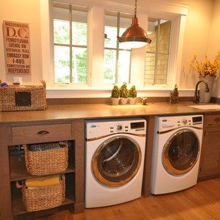 Esempio di una piccola sala lavanderia tradizionale con lavello sottopiano, ante a persiana, ante in legno scuro, pareti beige, parquet chiaro, lavatrice e asciugatrice affiancate e pavimento beige