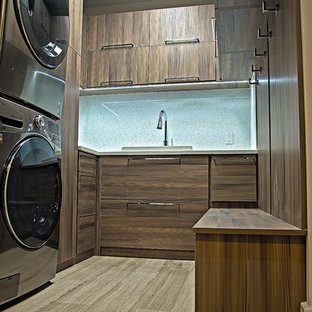 Inspiration for a mid-sized modern u-shaped dedicated laundry room in Miami with flat-panel cabinets, dark wood cabinets, a stacked washer and dryer, a drop-in sink, porcelain floors and beige floor.
