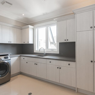 Large trendy l-shaped concrete floor and beige floor dedicated laundry room photo in Toronto with an undermount sink, flat-panel cabinets, gray cabinets, concrete countertops, beige walls and a side-by-side washer/dryer