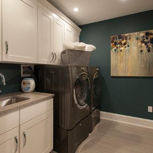 Cette image montre une grand buanderie parallèle design multi-usage avec un évier encastré, un placard à porte shaker, des portes de placard blanches, un sol en carrelage de porcelaine, des machines côte à côte, un sol gris et un mur bleu.