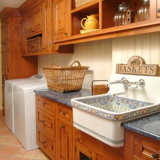 ミネアポリスのカントリー風おしゃれな洗濯室 (I型、エプロンフロントシンク、レイズドパネル扉のキャビネット、中間色木目調キャビネット、ベージュの壁、テラコッタタイルの床、左右配置の洗濯機・乾燥機、オレンジの床、青いキッチンカウンター) の写真