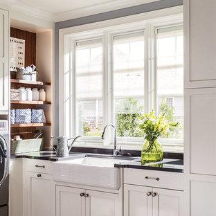 Klassisk inredning av en svarta u-formad svart tvättstuga enbart för tvätt, med en rustik diskho, skåp i shakerstil, vita skåp, grå väggar och en tvättmaskin och torktumlare bredvid varandra