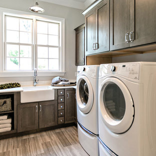Inspiration for a mid-sized craftsman l-shaped medium tone wood floor and gray floor dedicated laundry room remodel in Birmingham with a farmhouse sink, quartzite countertops, gray walls, a side-by-side washer/dryer, shaker cabinets, dark wood cabinets and white countertops