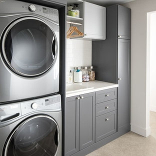 Photo of a mid-sized contemporary single-wall dedicated laundry room in Seattle with a drop-in sink, shaker cabinets, grey cabinets, quartz benchtops, white walls, carpet, a stacked washer and dryer, beige floor and white benchtop.