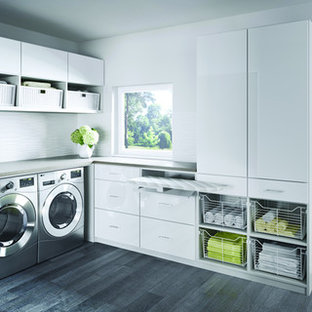 Inredning av ett klassiskt mellanstort l-format grovkök, med vita skåp, vita väggar, mörkt trägolv och en tvättmaskin och torktumlare bredvid varandra