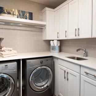 Inredning av en modern mellanstor l-formad tvättstuga enbart för tvätt, med en undermonterad diskho, luckor med profilerade fronter, vita skåp, laminatbänkskiva, vita väggar och en tvättmaskin och torktumlare bredvid varandra