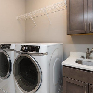 Inspiration for a mid-sized contemporary single-wall dedicated laundry room remodel in Other with an undermount sink, shaker cabinets, dark wood cabinets, quartz countertops, beige walls, a side-by-side washer/dryer and white countertops