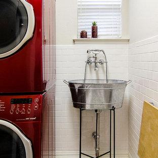 Klassisk inredning av en tvättstuga, med en allbänk, en tvättpelare, vita väggar, klinkergolv i keramik och vitt golv