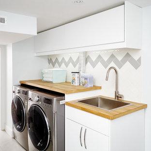 Imagen de cuarto de lavado lineal, nórdico, con fregadero encastrado, armarios con paneles lisos, puertas de armario blancas, encimera de madera, paredes blancas, lavadora y secadora juntas y encimeras beige